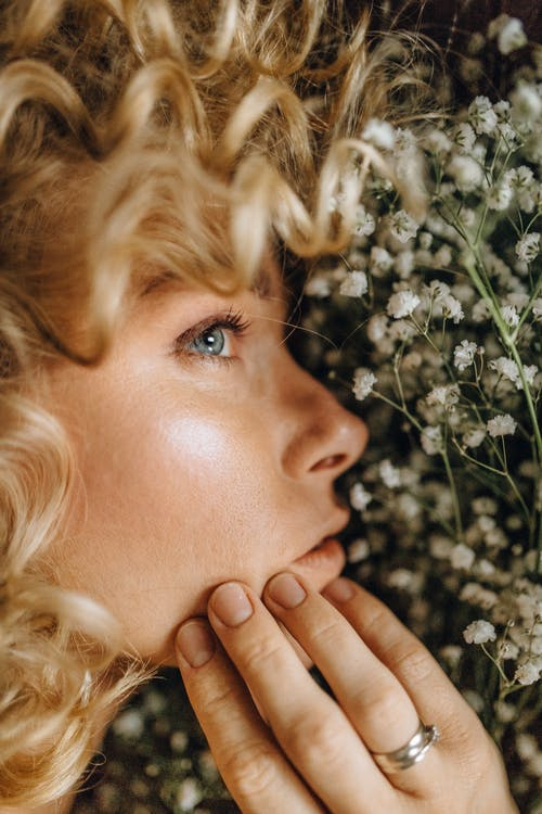 Close-Up Photo of Woman's Face Near White Flowers