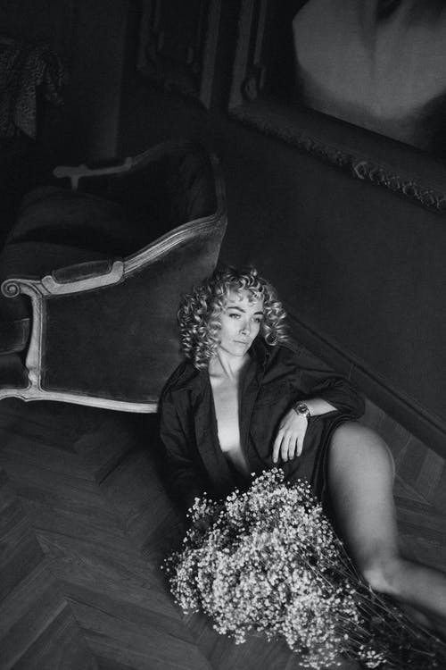 Monochrome Photo of Woman Lying on Floor Near Flowers
