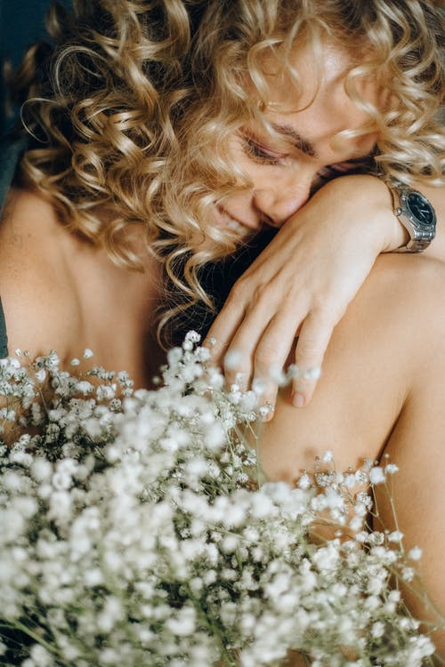 Photo of Woman Smiling Near White Flowers