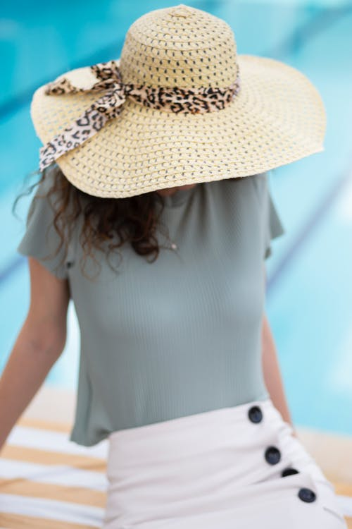 Woman in White Sleeveless Dress Wearing White and Brown Sun Hat