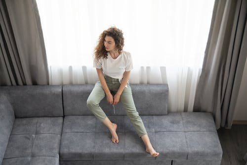 Woman in White Crew Neck T-shirt and Gray Pants Sitting on Gray Couch