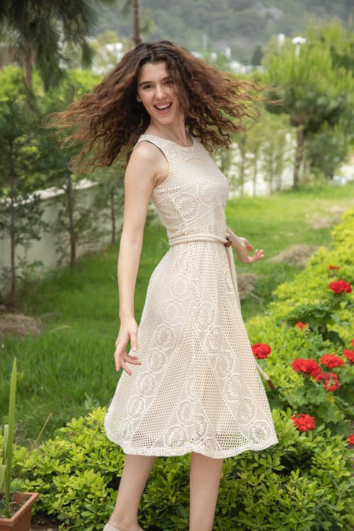 Woman in White Floral Sleeveless Dress Standing on Green Grass Field