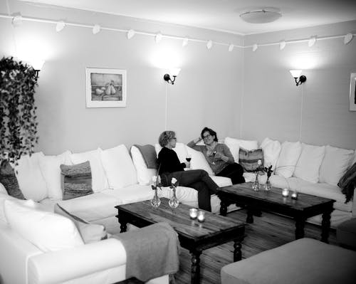 Female friends resting and drinking wine in living room