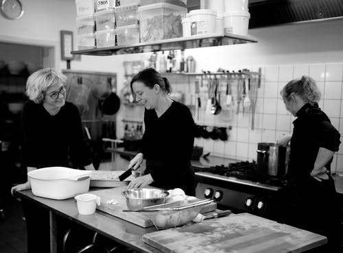 Black and white company of female cooks preparing food in kitchen of cafe while interacting and smiling