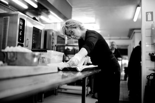 Black and white concentrated female chef standing at metal table in kitchen and preparing food in restaurant