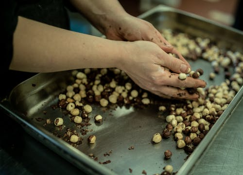 Crop woman with nuts in kitchen of cafe