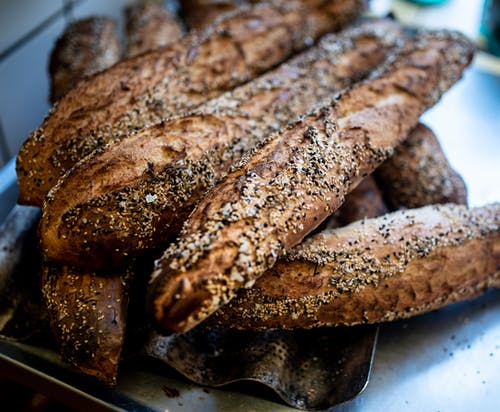 Closeup of delicious crunchy baguettes placed on metal counter in kitchen of bake house