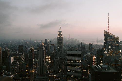 City Skyline Under Gray Sky during Night Time