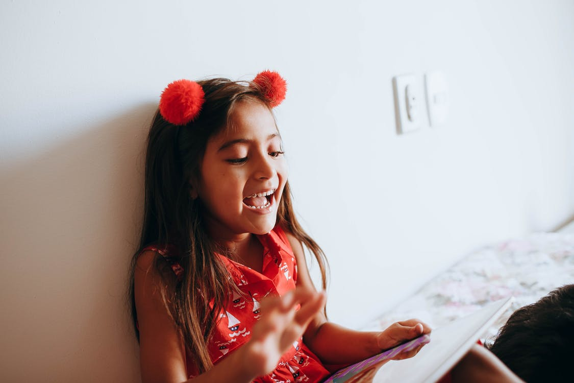 Photo of Girl Leaning on White Wall While Playing With Tablet Computer