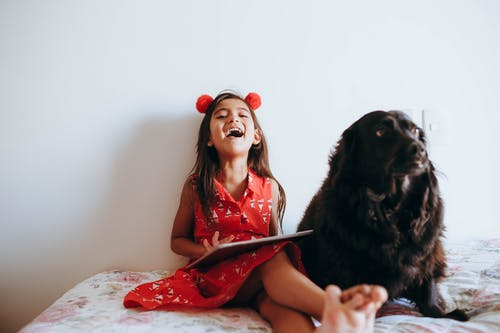 Photo of Girl Sitting Beside Black Dog