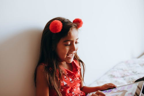 Photo of Girl Playing With Tablet Computer