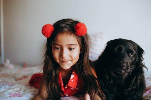 Photo of Girl Lying Beside Black Dog