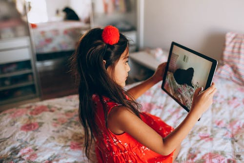 Photo of Girl in Red Dress Taking Photo Using Tablet Computer