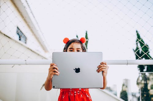 Photo of Girl in Red Dress Holding Silver Ipad Pro