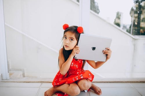 Girl in Red Dress Sitting While Holding Silver Ipad Pro
