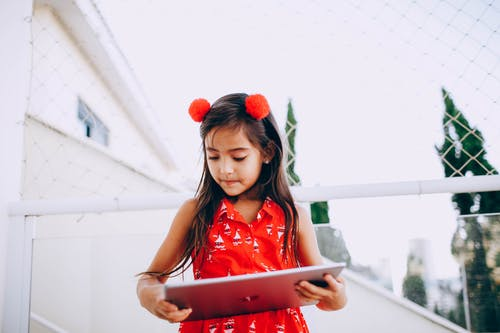 Smart child browsing tablet on street