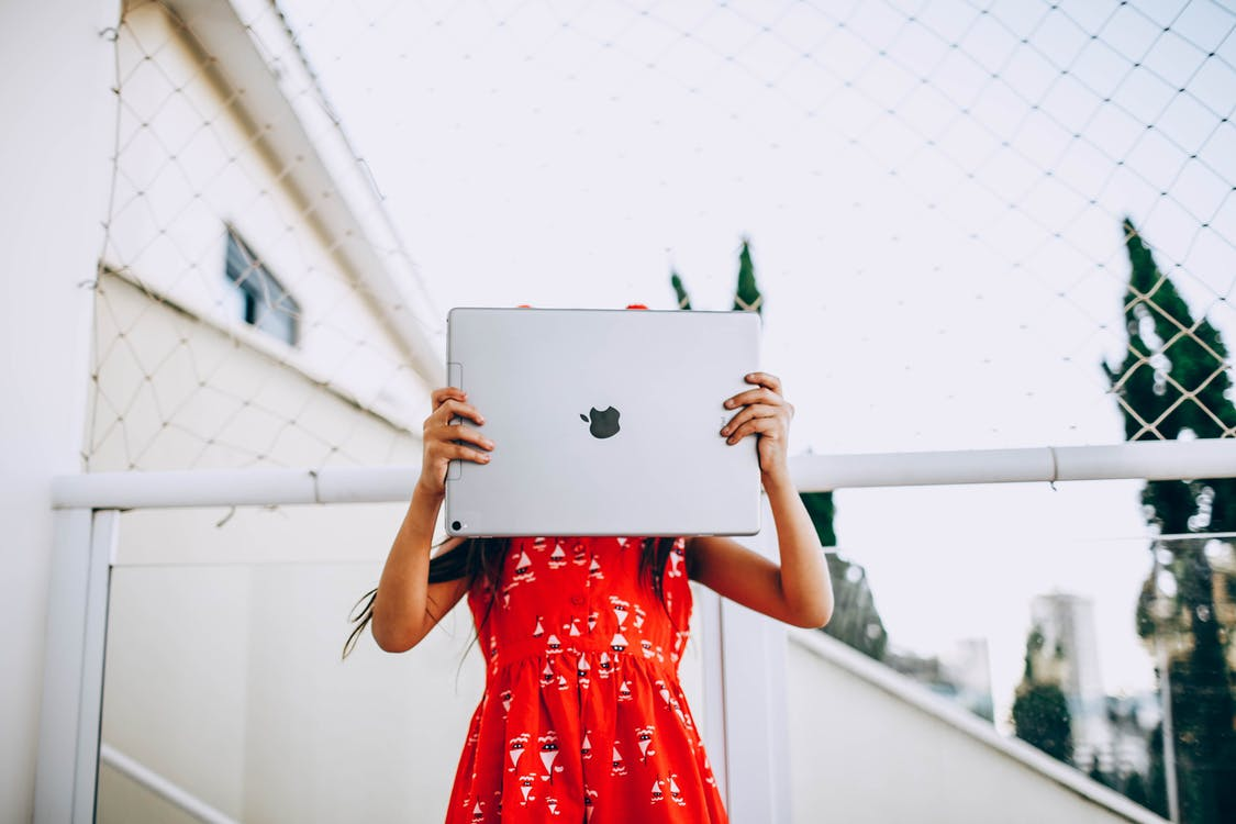 Woman in Red Dress Holding Silver Macbook
