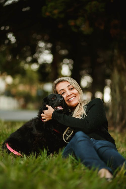 Smiling woman with cute dog on lawn