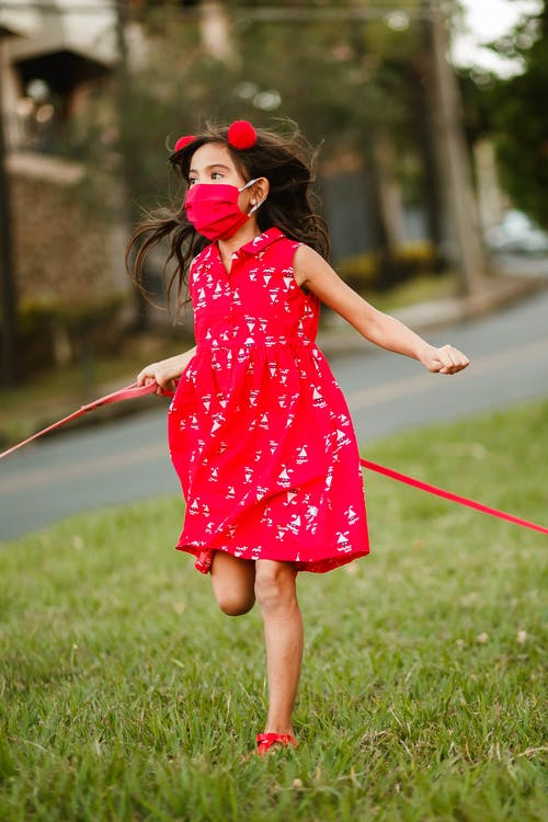 Carefree child in summer dress and medical mask running along green meadow in city and enjoying freedom while looking away