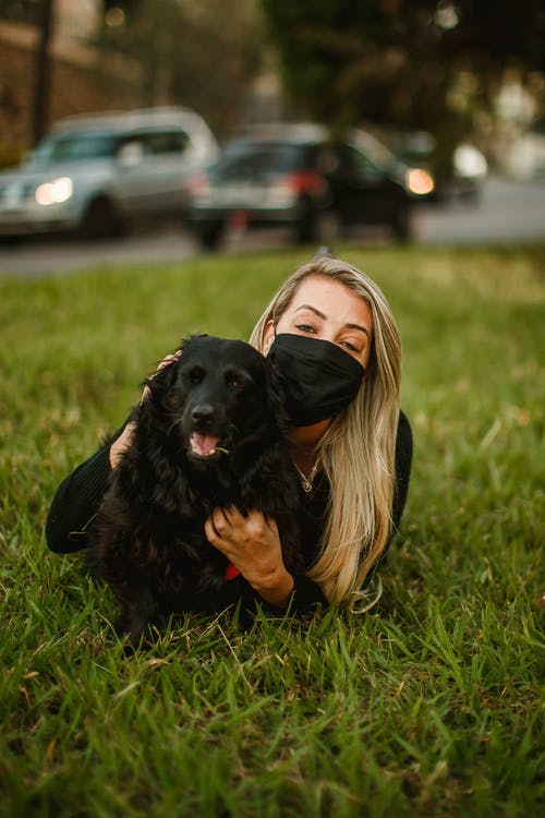 Woman in mask with dog on meadow