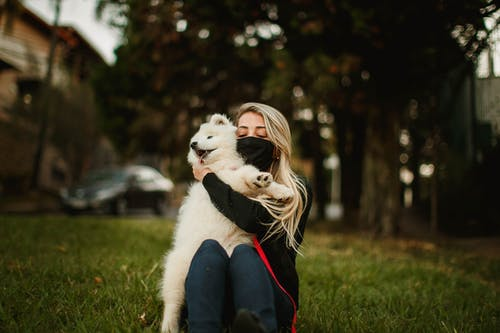 Relaxed female in medical mask sitting on lawn and cuddling adorable fluffy dog during stroll in park