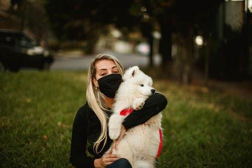 Serene woman hugging cute dog in city