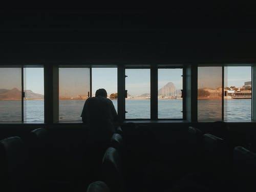 Silhouette of Man Sitting on Chair Near Body of Water