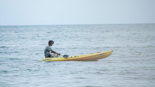 Man in Black Jacket Riding Yellow Kayak on Sea
