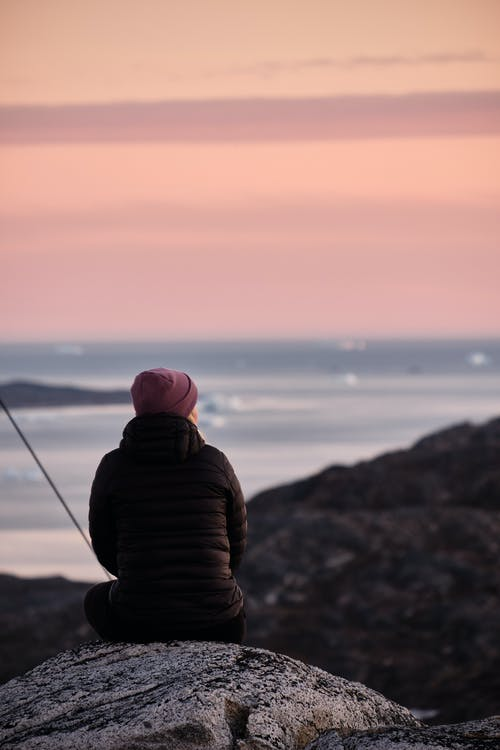 Anonymous traveler on stone contemplating sea at sunset