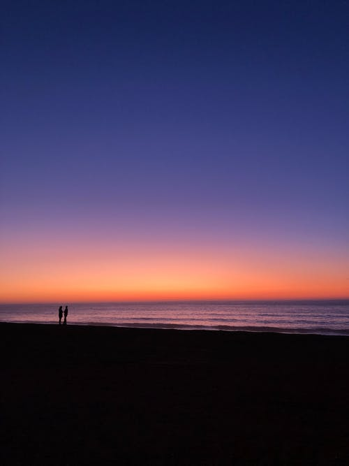 Endless sea under colorful sky at sundown