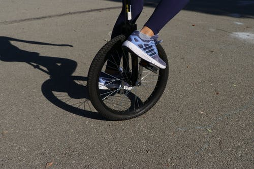 Crop person riding unicycle on asphalt road