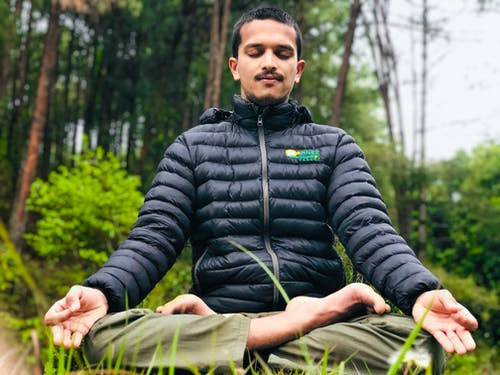 Mindful ethnic man sitting in Lotus pose in forest