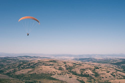 Person in Parachute over Brown Mountains