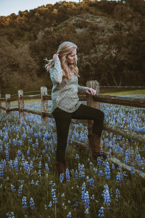 Woman in White Knit Sweater and Black Pants Standing on Blue Flower Field