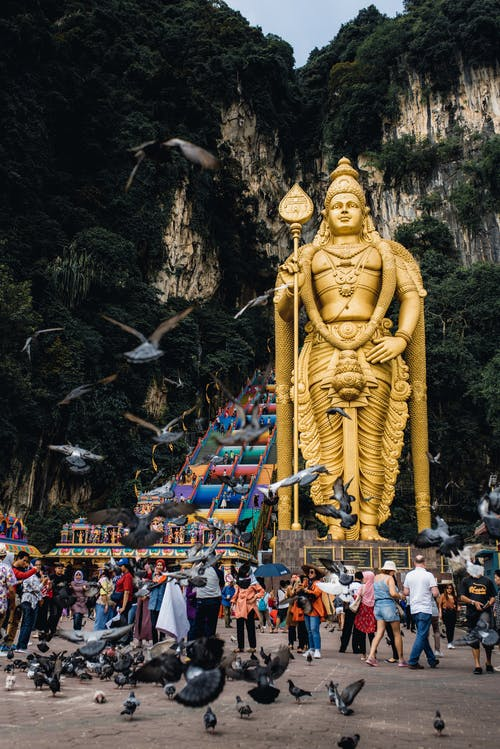 Batu Caves with Murugan statue and tourists walking on square