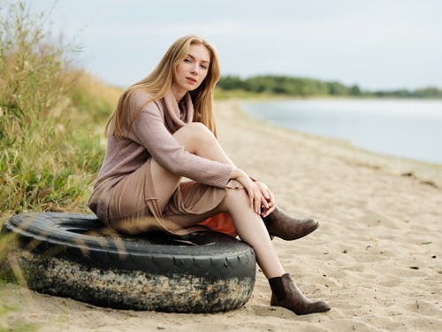 Woman in Brown Long Sleeve Shirt and Black Pants Sitting on Rock Near Body of Water