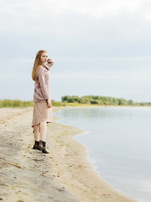 Woman in Pink Long Sleeve Dress Standing on Brown Sand Near Body of Water