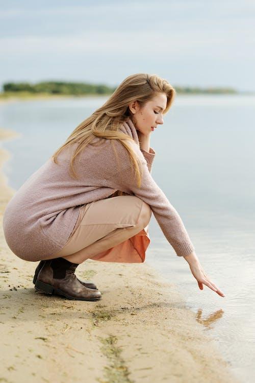 Frau In Der Braunen Robe, Die Auf Braunem Sand Nahe Körper Des Wassers Sitzt