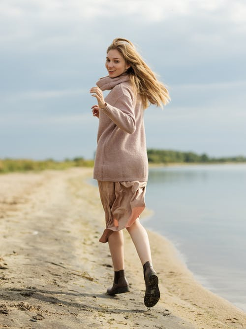Woman in Pink Long Sleeve Shirt and Brown Skirt Standing on Beach Shore