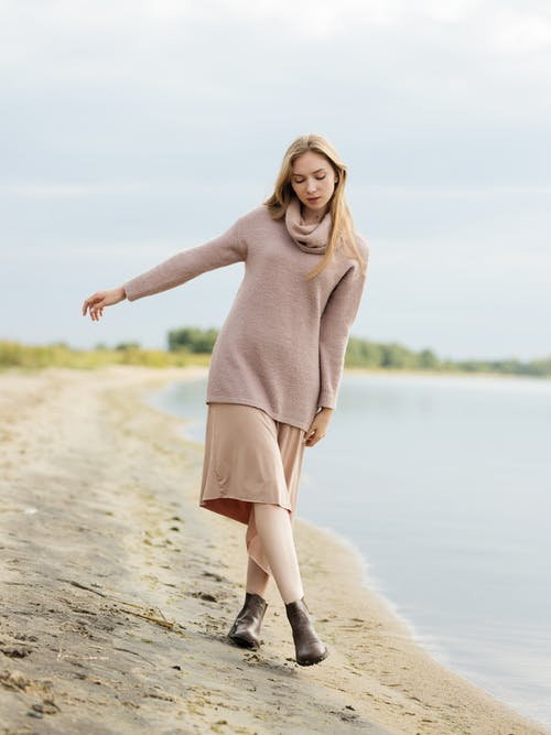 Woman in Brown Long Sleeve Dress Standing on Gray Rock Near Body of Water