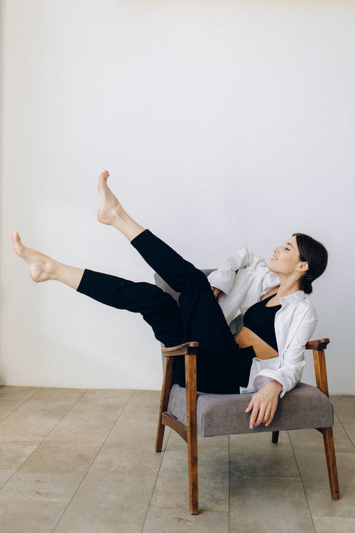 Woman in White Shirt and Black Pants Sitting on Brown Wooden Armchair