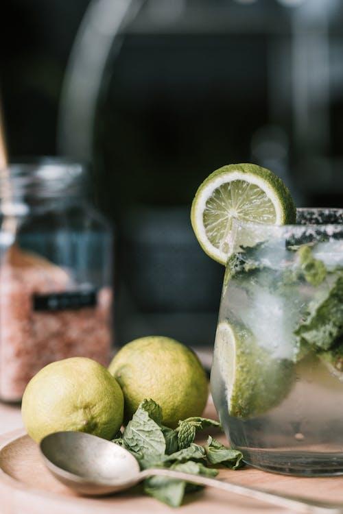 Green Lemon Fruit Beside Clear Glass Jar