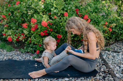 Mother and son resting on yoga mat in garden