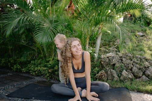 Cheerful smiling sportswoman sitting in lotus pose with adorable little son on yoga mat in green tropical garden
