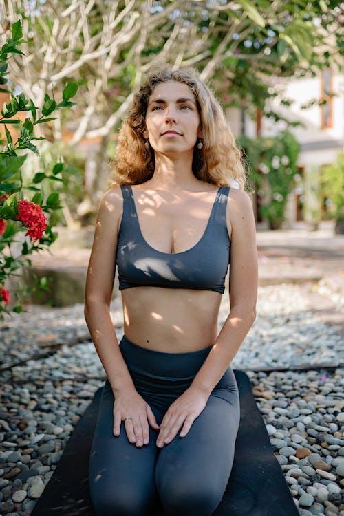 Content sportswoman sitting on yoga mat in garden