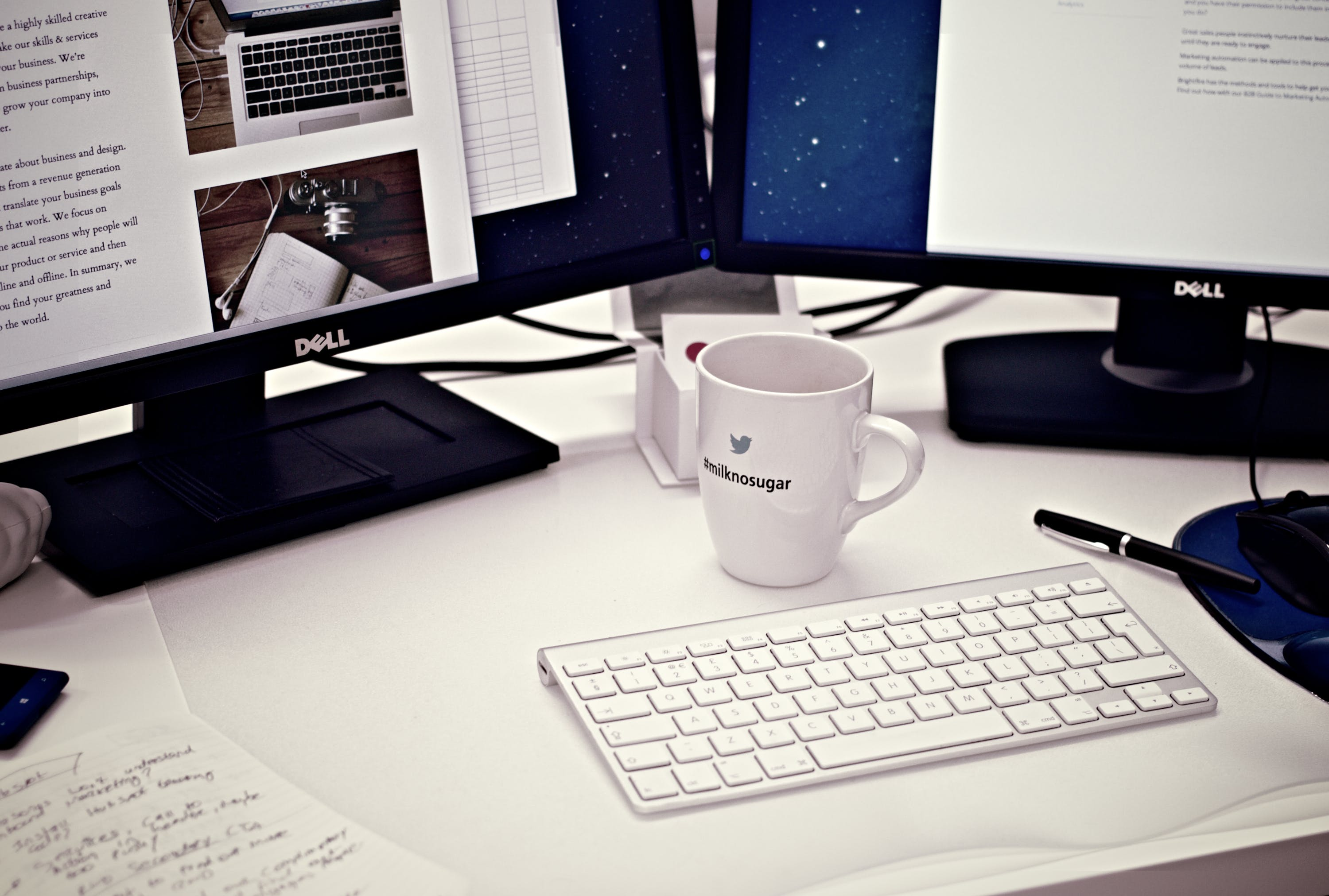 White Ceramic Mug Between Apple Magic Keyboard and Two Flat Screen Computer Monitors