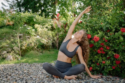 Young woman practicing yoga in garden with blooming shrubs