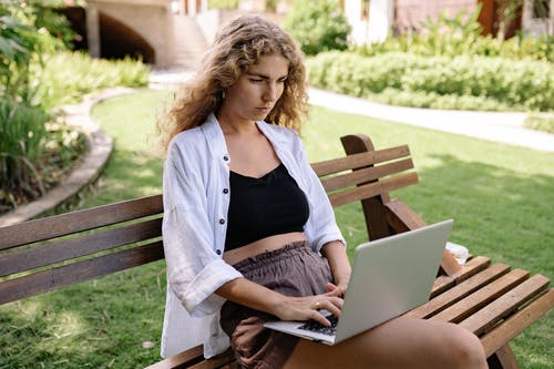 Photo of Woman Sitting on Wooden Bench While Using Silver Laptop