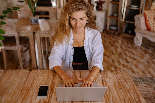 Photo of Woman Using Silver Laptop While Smiling