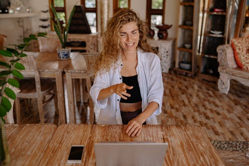 Photo of Woman Smiling While Looking at Silver Laptop